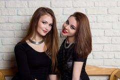 dos chicas jóvenes hermosas en vestidos negros se sientan en el banco y el chisme Fotos de archivo libres de regalías