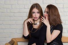 dos chicas jóvenes hermosas en vestidos negros se sientan en el banco y el chisme Imagen de archivo