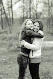 Dos chicas jóvenes hermosas que abrazan en la primavera Imagenes de archivo
