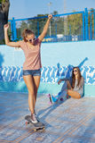 Dos chicas jóvenes hermosas que desgastan las gafas de sol en una piscina vacía Imágenes de archivo libres de regalías