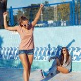 Dos chicas jóvenes hermosas que desgastan las gafas de sol en una piscina vacía Imagen de archivo libre de regalías