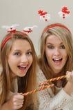 Dos chicas jóvenes hermosas que disfrutan y que se divierten con la Navidad Foto de archivo