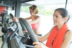 Dos chicas jóvenes hermosas que ejercitan junto en gimnasio Imágenes de archivo libres de regalías