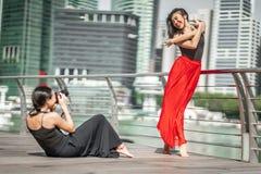 Dos chicas jóvenes hermosas que tienen tiroteo de foto de la diversión en los wi de una cubierta Foto de archivo libre de regalías