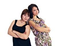 Dos chicas jóvenes inclinadas hombro con hombro con uno a foto de archivo libre de regalías