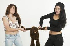 Dos chicas jóvenes juguetonas con un oso de peluche Fotos de archivo