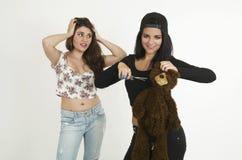 Dos chicas jóvenes juguetonas con un oso de peluche Imagenes de archivo