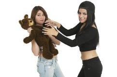 Dos chicas jóvenes juguetonas con un oso de peluche Fotos de archivo libres de regalías