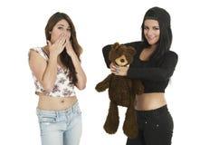 Dos chicas jóvenes juguetonas con un oso de peluche Foto de archivo