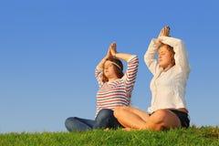 Dos chicas jóvenes meditate en la hierba verde foto de archivo