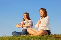 Dos chicas jóvenes meditate y reflejan en la hierba fotos de archivo