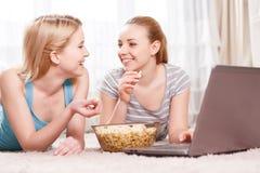 Dos chicas jóvenes que comen las palomitas Imagen de archivo