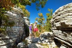Dos chicas jóvenes que exploran el bosque de piedra, formación de roca natural, creada por las capas múltiples de piedra, situada fotografía de archivo libre de regalías