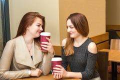 Dos chicas jóvenes que hablan en una cafetería Imágenes de archivo libres de regalías