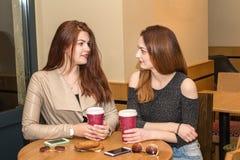 Dos chicas jóvenes que hablan en una cafetería Fotos de archivo libres de regalías
