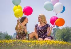 Dos chicas jóvenes que mienten en la hierba Foto de archivo