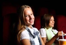 Dos chicas jóvenes que miran en cine Foto de archivo