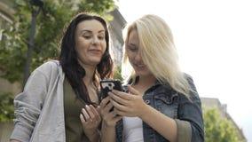 Dos chicas jóvenes que ríen y que enrollan la pantalla táctil del smartphone que mira algo divertido en medios sociales almacen de video