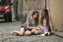 Dos chicas jóvenes que se sientan con un gato en el pavimento Fotografía de archivo