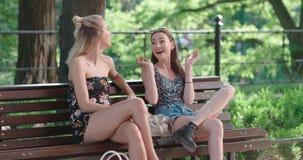 Dos chicas jóvenes que se sientan en banco en un parque que disfruta de verano y de la charla Fotos de archivo libres de regalías