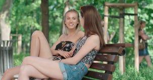 Dos chicas jóvenes que se sientan en banco en un parque que disfruta de verano y de la charla Imagen de archivo libre de regalías
