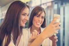 Dos chicas jóvenes que se sientan en café usando el teléfono elegante Fotos de archivo