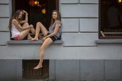 Dos chicas jóvenes que se sientan en el alféizar que el club de noche en la tarde mide el tiempo Imagen de archivo libre de regalías