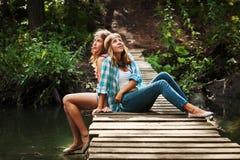 Dos chicas jóvenes que se sientan en el puente de madera Fotografía de archivo