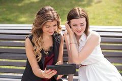 Dos chicas jóvenes que se sientan en un banco en un parque que mira la tableta y la risa Imágenes de archivo libres de regalías