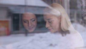 Dos chicas jóvenes que se sientan en un café, visión desde la calle a través del vidrio almacen de metraje de vídeo