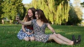 Dos chicas jóvenes que se sientan en una naturaleza tiran selfies y la diversión el tener metrajes
