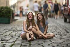 Dos chicas jóvenes que se sientan junto en el pavimento de piedra Imágenes de archivo libres de regalías