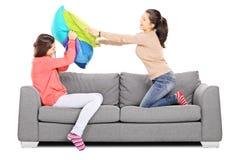 Dos chicas jóvenes que tienen una lucha de almohada asentada en el sofá Fotos de archivo libres de regalías