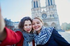 Dos chicas jóvenes que toman el selfie cerca de Notre-Dame en París Foto de archivo