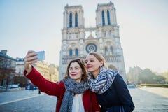 Dos chicas jóvenes que toman el selfie cerca de Notre-Dame en París Fotos de archivo