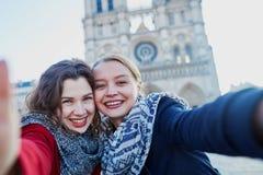 Dos chicas jóvenes que toman el selfie cerca de Notre-Dame en París Fotografía de archivo