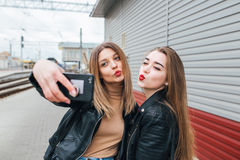 Dos chicas jóvenes que toman el selfie usando smartphone Imagen de archivo libre de regalías