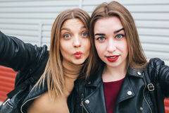 Dos chicas jóvenes que toman el selfie usando smartphone Foto de archivo libre de regalías