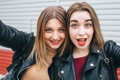 Dos chicas jóvenes que toman el selfie usando smartphone Foto de archivo