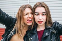 Dos chicas jóvenes que toman el selfie usando smartphone Imagenes de archivo