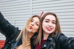Dos chicas jóvenes que toman el selfie usando smartphone Fotos de archivo libres de regalías