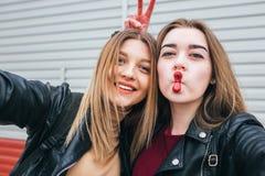 Dos chicas jóvenes que toman el selfie usando smartphone Fotografía de archivo