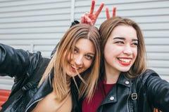 Dos chicas jóvenes que toman el selfie usando smartphone Fotos de archivo