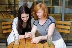 Dos chicas jóvenes que usan el teléfono elegante foto de archivo libre de regalías