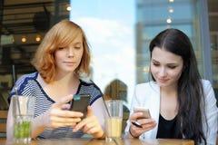 Dos chicas jóvenes que usan su teléfono elegante fotos de archivo libres de regalías