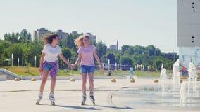 Dos chicas jóvenes Rollerblading en un parque metrajes