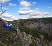 Dos chicas jóvenes se sientan encima de una montaña y estudian el mapa Fotos de archivo