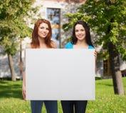 Dos chicas jóvenes sonrientes con el tablero blanco en blanco Fotos de archivo libres de regalías