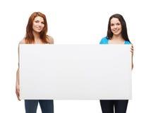 Dos chicas jóvenes sonrientes con el tablero blanco en blanco Foto de archivo libre de regalías