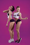 Dos chicas jóvenes sonrientes de la aptitud en fondo rosado Imagenes de archivo